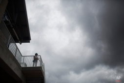 A baseball fan watches as rain clouds move in over Hammond Stadium in the sixth inning of an exhibition spring training baseball game between the Minnesota Twins and the Pittsburgh Pirates, Friday, March 27, 2015, in Fort Myers, Fla. (AP Photo/Brynn Anderson)