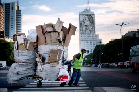A man who collects cardboard boxes for recycling pulls his cart in Buenos Aires, Argentina, Thursday, Dec. 19, 2013. Behind, a building is decorated with an image of Argentina's former first lady and leader Eva Peron. (AP Photo/Rodrigo Abd)