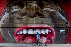 """A man with a cart passes in front of a street painting in Buenos Aires, Argentina, Monday, Oct. 21, 2013. The mural, by artist Alfredo Segatori, known as """"Pelado"""", covers a wall of a bridge in the Palermo neighborhood. (AP Photo/Natacha Pisarenko)"""