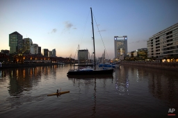 A person kayaks near boats moored at the Yacht Club Puerto Madero in Buenos Aires, Argentina, Wednesday, Sept. 12, 2012. (AP Photo/Natacha Pisarenko)