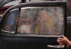 Filipino children play inside an abandoned car in Manila, Philippines on Tuesday, Feb. 24, 2015. (AP Photo/Aaron Favila)