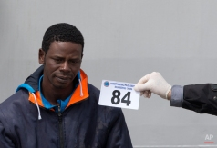 An Italian forensic police officer holds a numbered tag as he identifies a man who disembarked from the Italian Coast Guard ship ' Fiorillo ' at the Catania harbor, Sicily, southern Italy, Friday, April 24, 2015. The European Union's border agency Frontex is to send its ships further into the Mediterranean Sea in response to a deadly exodus of migrants leaving Libya. (AP Photo/Alessandra Tarantino)