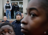 Members of the Baltimore Police Department stand guard outside the department's Western District police station during a protest for Freddie Gray, Thursday, April 23, 2015, in Baltimore. Gray died from spinal injuries about a week after he was arrested and transported in a police van. (AP Photo/Patrick Semansky)