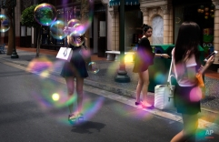 A tourist takes pictures amidst soap bubbles from a mist blowing machine at Universal Studios, a popular tourist destination, Wednesday, April 8, 2015, in Sentosa, Singapore. The city-state's government announced new plans for its global marketing campaign to tap on the country's year-long 50th birthday celebration, as part of its continued effort to boost tourism numbers in 2015, after the country went through a challenging season in 2014. (AP Photo/Wong Maye-E)