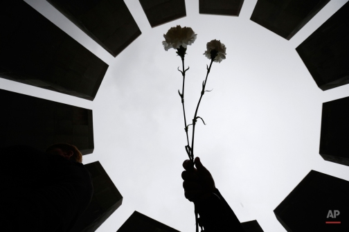 People lay flowers at a memorial to Armenians killed by the Ottoman Turks, as they mark the centenary of the mass killings, in Yerevan, Armenia, Friday, April 24, 2015. Armenians on Friday marked the centenary of what historians estimate to be the slaughter of up to 1.5 million Armenians by Ottoman Turks, an event widely viewed by scholars as genocide. Turkey, however, denies the deaths constituted genocide and says the death toll has been inflated. (AP Photo/Sergei Grits)