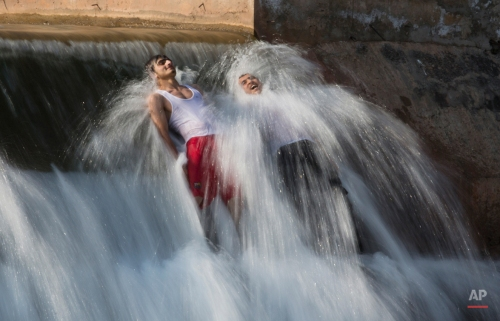 Pakistani men bathe in a stream to beat the heat on the outskirts of Islamabad, Pakistan, Wednesday, April 8, 2015. (AP Photo/B.K. Bangash)