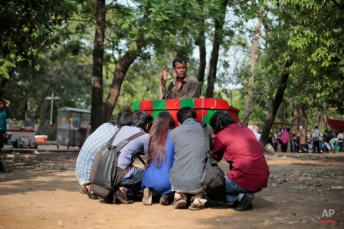 Bangladeshi man Muhammad Jalil, 52, plays a music instrument with his right hand, as he uses his left hand to run his handmade picture machine called the bioscope, into which youth peep to look at moving images at a park in Dhaka, Bangladesh, Wednesday, April 8, 2015. Jalil who hails from Rajshahi district has arrived in the Bangladeshi capital hoping to attract customers ahead of the Bangla New Year that falls on April 15. This yesteryear entertainer takes out this traditional instrument, handed down to him through generations, only during festival seasons owing to the waning interest among the public. (AP Photo/ A.M. Ahad)