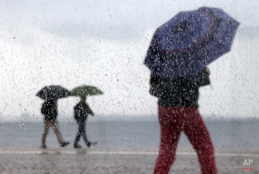 People, photographed through a window with raindrops, shelter under umbrellas against the rain as they walk near the Tagus riverbank in Lisbon, Wednesday, April 8, 2015. The city promenade is a popular riverside walking path where people stroll or enjoy fishing. (AP Photo/Francisco Seco)