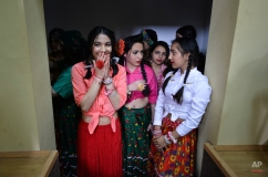 Romanian Roma wait to perform on stage during an International Day of the Roma event in Glina, Romania, Wednesday, April 8, 2015. Romania is home to one of the largest Gypsy, or Roma, communities in Europe, counting more than 600,000 people according to official statistics, actual numbers are likely to be higher since many do not declare their ethnicity in censuses fearing discrimination.(AP Photo/Andreea Alexandru, Mediafax)