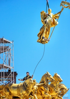 The charioteer figure, Prosperity, who guides the golden horses on the Minnesota State Capitol building's Quadriga statue, is lifted back into its position, Wednesday, April 29, 2015, in St. Paul, Minn. The figure was removed last year for repairs. (Glen Stubbe/Star Tribune via AP)