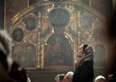 A woman belonging to Romania's Armenian community attends a religious service in memory of Armenians killed by the Ottoman Turks, as she and fellow Armenians mark the centenary of the mass killings, in Bucharest, Romania, Friday, April 24, 2015. Armenians on Friday marked the centenary of what historians estimate to be the slaughter of up to 1.5 million Armenians by Ottoman Turks, an event widely viewed by scholars as genocide. Turkey, however, denies the deaths constituted genocide and says the death toll has been inflated. (AP Photo/Vadim Ghirda)
