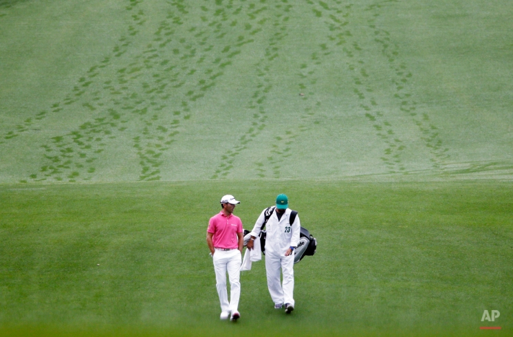 Mike Weir, of Canada, walk with his caddie down the first fairway during a practice round for the Masters golf tournament Wednesday, April 8, 2015, in Augusta, Ga. (AP Photo/Matt Slocum)
