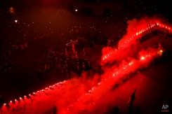 In this photo taken on Monday, March 30, 2015, red flares burn while penitents of the Cristo de Viga brotherhood carrying a float with a cross take part in a Holy Week procession in Jerez de la Frontera, Spain, Monday, March 30, 2015. (AP Photo/Daniel Ochoa de Olza)