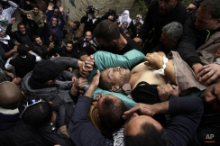 Mourners carry the body of Ziyad Awad during his funeral in Beit Ummar, West Bank, Friday, April 10, 2015. Awad was killed in clashes with Israeli soldiers following a funeral of his cousin who died three months after being released from Israeli jail. (AP Photo/Mahmoud Illean)