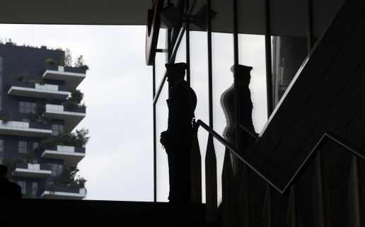 A Carabineri (Italian paramilitary police) officer patrols the Porta Nuova business district as the Bosco Verticale (Vertical Forest) building is visible in background, in Milan, Italy, Wednesday, April 29, 2015. Milan has been growing in altitude in preparation for Expo 2015 world's fair opening next Friday with the construction of a dozen new skyscrapers in recent years. City leaders hope a successful world's fair, expected to attract 20 million visitors over the six-month run, will help Italy's fashion and banking capital grow in international stature as well. The most optimistic see the event as a stimulus to help boost Italy out of economic doldrums. (AP Photo/Luca Bruno)