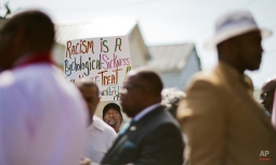 Jerome Smalls, of Charleston, S.C., holds up a sign during a news conference outside the Charleston NAACP office regarding the shooting death of Walter Scott by a North Charleston police officer, Thursday, April 9, 2015, in Charleston S.C. The officer, Michael Thomas Slager, has been fired and charged with murder. (AP Photo/David Goldman)