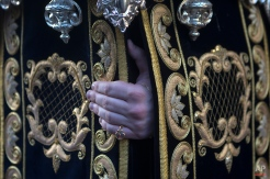 In this photo taken on Sunday, March 29, 2015, the hand of a penitent from Los Estudiantes brotherhood gets a grip on a platform that several penitents carry with an statue of the Virgin Mary during a Palm Sunday Holy week procession in Madrid, Spain. (AP Photo/Paul White)