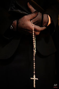 """In this photo taken on Thursday, April 2, 2015, hand of a Penitents raises a rosary beads as she takes part in the procession of the """"Exaltacion de La Santa Cruz"""" brotherhood, during Holy Week in Zaragoza, northern Spain. (AP Photo/Alvaro Barrientos)"""