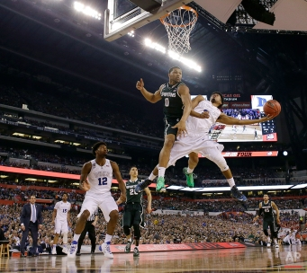 Duke's Quinn Cook, right, is fouled by Michigan State's Marvin Clark Jr. (0) while driving to the basket during the second half of the NCAA Final Four tournament college basketball semifinal game Saturday, April 4, 2015, in Indianapolis. (AP Photo/David J. Phillip)
