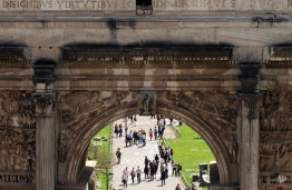 Tourists walk under the Septimius Severus arch, dating back to 203 AD, in the ancient Roman Forum in Rome, April 12, 2015. (AP Photo/Angela Gennaro)