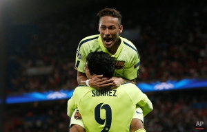Barcelona's Luis Suarez, rear, celebrates with Neymar after Suarez scored his team's third goal during the quarterfinal first leg Champions League soccer match between Paris Saint Germain and Barcelona at the Parc des Princes stadium in Paris, France, Wednesday, April 15, 2015. (AP Photo/Christophe Ena)
