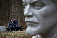 An elderly couple sit next to a statue of Soviet Union founder Vladimir Lenin during celebration of his 145th birthday at the Lenin Hut Museum at Razliv lake, outside St.Petersburg, Russia, Wednesday, April 22, 2015. (AP Photo/Dmitry Lovetsky)