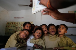 School children listen to their teacher at a government-run school in Allahabad, India, Thursday, April 9, 2015. According to the UNESCO Education for All Global Monitoring Report 2015, two out of three countries where lower secondary education was not compulsory in 2000 had changed their legislation by 2012, including India, Indonesia, Nigeria and Pakistan. According to the report, rural India saw substantial improvement in nearly all aspects of school facilities and infrastructure between 2003 and 2010. (AP Photo/ Rajesh Kumar Singh)