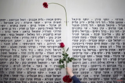 A boy hangs a rose on the wall of names of fallen soldiers, at the Armored Corps memorial, before a ceremony marking the annual Memorial Day for soldiers and civilians killed in more than a century of conflict between Jews and Arabs, in Latrun near Jerusalem, Israel, Wednesday, April 22, 2015. Israel came to a standstill on Wednesday as sirens wailed across the country on its annual Memorial Day for fallen soldiers and victims of terrorism. (AP Photo/Ariel Schalit)