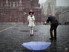 Chinese tourists take photographs at Red Square during a snowfall in Moscow, Russia, April 3, 2015. (AP Photo/Alexander Zemlianichenko)