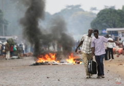 Two men carry a suitcase past a burning barricade in Bujumbura, Burundi, Thursday, April 30, 2015, after the government issued and ordered for all university campuses to close down. Bujumbura has been hit by street protests since Sunday as the security forces confront demonstrators who say a third term for President Pierre Nkurunziza would violate the country's constitution. (AP Photo/Jerome Delay)
