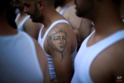 """In this photo taken on Tuesday, March 31, 2015, """"costaleros"""" from """"Dulce Nombre"""" brotherhood, who carry the portable platform which supports a statue of Jesus Christ on his back, wait outside the church to take part in a procession in Seville, Spain. (AP Photo/Emilio Morenatti)"""