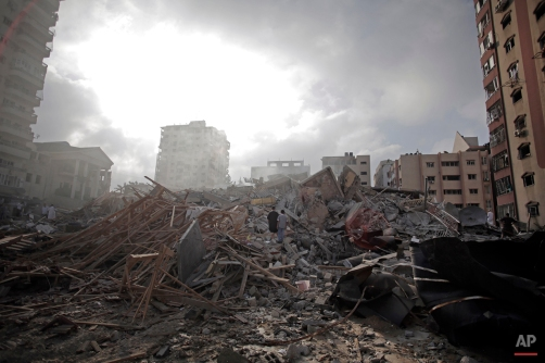 Palestinians inspect the rubble of the Al-Zafer apartment tower following Israeli airstrikes Saturday that collapsed the 12-story building, in Gaza City, Aug. 24, 2014. (AP Photo/Khalil Hamra)