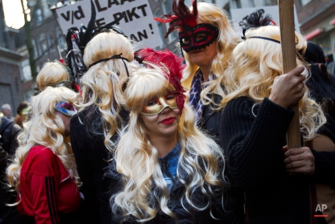Masked women hold banners as prostitutes and sympathizers take to the streets to protest plans to clean up the city's famed red light district by shuttering windows where scantily-clad sex workers pose to attract clients, Amsterdam, Netherlands, Thursday, April 9, 2015. Prostitutes say that the closures are depriving them of safe places to work. (AP Photo/Peter Dejong)