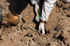 An Iraqi forensic worker excavates human remains in a mass grave, believed to contain the bodies of Iraqi soldiers killed by Islamic State group militants when they overran Camp Speicher military base last June, in Tikrit, Iraq, 80 miles (130 kilometers) north of Baghdad, Thursday, April 9, 2015. (AP Photo/Karim Kadim)