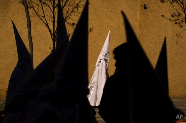In this photo taken on Sunday, March 29, 2015, hooded penitents from the La Paz brotherhood walk to the church to take part in a procession in Seville, Spain. (AP Photo/Emilio Morenatti)