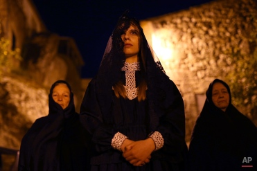 In this photo taken on Friday, April 3, 2015, a woman playing the roll of Mary Magdalene takes part in a procession during the Holy Week celebrations in the small town of Monsanto, near Idanha-A-Nova, Portugal. (AP Photo/Francisco Seco)