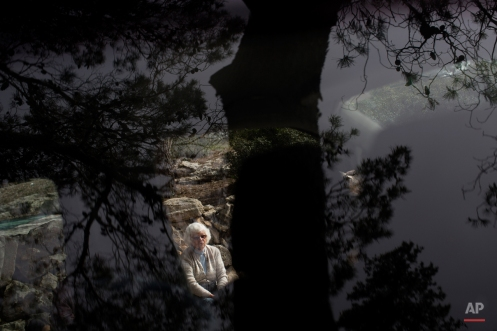 Holocaust survivor Ester Reiss is seen through a car window, as she tells her personal testimony to Israeli border police officers, during a ceremony marking the annual Holocaust remembrance day in the Martyr's forest near Moshav Kesalon, in central Israel, Thursday, April 16, 2015. Sirens sounded across Israel on Thursday morning, bringing life to a standstill as millions of Israelis observed a moment of silence to honor the memory of the 6 million Jews killed in the Nazi Holocaust during World War II. (AP Photo/Oded Balilty)
