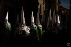 In this photo taken on Thursday, April 2, 2015, penitents of the 'Virgen de la Esperanza' brotherhood march as they take part in a Holy Week procession in Zamora, Spain. (AP Photo/Andres Kudacki)