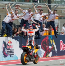 Marc Marquez, of Spain, rides by his crew after winning the MotoGP Grand Prix motorcycle race at the Circuit of the Americas, Sunday, April 12, 2015, in Austin, Texas. (AP Photo/Darren Abate)