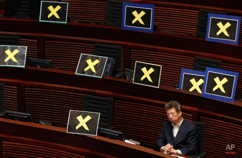 Pro-democracy lawmaker Ronny Tong sits with placards of yellow crosses placed after the lawmakers walk out of the legislative chamber to protest against Chief Secretary Carrie Lam who unveiled the Beijing-backed election reform package's details, in Hong Kong, Wednesday, April. 22, 2015. Hong Kong's government unveiled the election reform proposals that would allow residents to vote for the southern Chinese city's top leader for the first time. But the proposals include Beijing-backed restrictions facing stiff resistance from the city's pro-democracy lawmakers. (AP Photo/Vincent Yu)