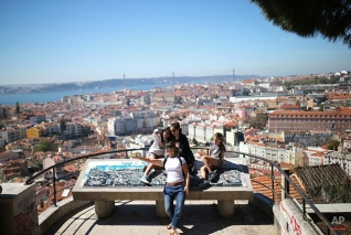 """Tourists pose for a selfie at the Nossa Senhora do Monte or """"Our Lady of the Hill"""" viewpoint overlooking Lisbon, Portugal, April 1, 2015. (AP Photo/Francisco Seco)"""