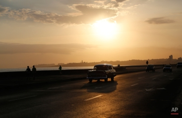 A taxi driver steers his classic American car along the Malecon at sunrise in Havana, Cuba, Wednesday, April 15, 2015. Cuban officials and ordinary citizens alike hailed the island's removal from the U.S. list of state sponsors of terrorism, saying the move by President Barack Obama heals a decades-old insult to national pride and clears the way to swiftly restore diplomatic relations. (AP Photo/Desmond Boylan)