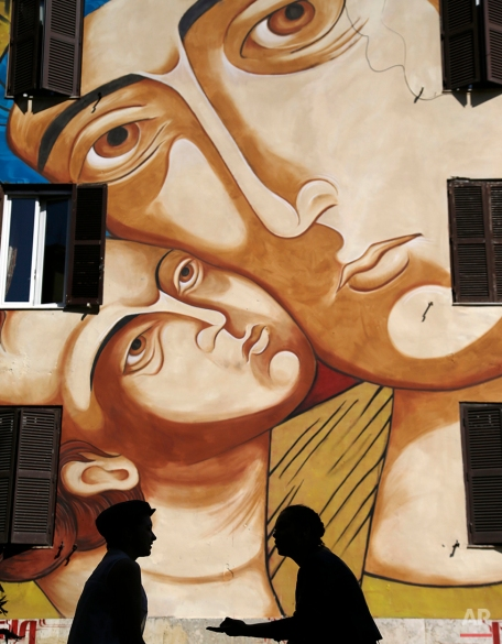 """Youths are silhouetted against the mural """"Holy Mary of Shanghai"""", by street artist Mr. Klevra, painted on the facade of a public housing building in Rome, April 13, 2015. (AP Photo/Gregorio Borgia)"""