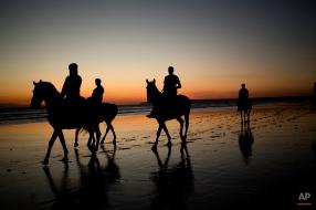 Tourists ride horses along the beach as the sun sets in Cadiz the south of Spain, April 1, 2015. (AP Photo/Emilio Morenatti)