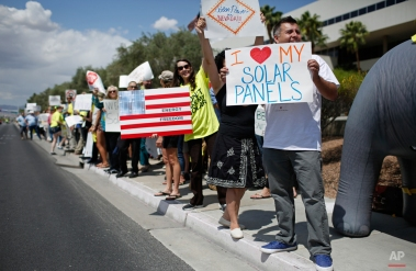 Protestors, including Ronald Brittan, right, line up along the street during a rally in front of NV Energy Wednesday, April 22, 2015, in Las Vegas. Hundreds of activists gathered outside NV Energy headquarters in Las Vegas to protest a state cap affecting rooftop solar installations and urge the Legislature to lift it. (AP Photo/John Locher)