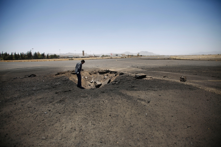 A Yemeni man looks at a crater, at the Sanaa International airport, in Yemen, Wednesday, April 29, 2015. Saudi-led coalition warplanes pounded Shiite rebels and their allies overnight and throughout the day on Tuesday in the Yemeni capital. Around midday, airstrikes hit Sanaa International airport, setting a plane owned by a private company on fire, according to a statement released by the Shiite rebels, known as Houthis. (AP Photo/Hani Mohammed)