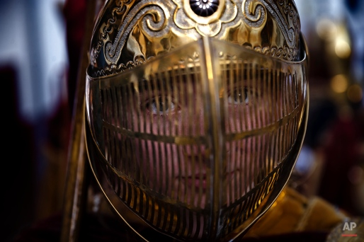 In this photo taken on Thursday, April 2, 2015, a penitent wears a golden helmet, part of her costume of Roman empire's soldier, as she takes part on the 'Estacion Penitencial de Nuestro Padre Jesus Nazareno Cautivo' Holy Week procession in Arriate, Spain. (AP Photo/Daniel Ochoa de Olza)