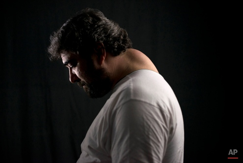 """In this image taken on Thursday, March 12, 2015 Luismi Fajardo, 45, poses for a photo showing a hump developed during his years as costalero, during a practice run in Seville. Fajardo, a costalero from the """"Macarena"""" brotherhood, who carries the portable platform which supports a statue of Jesus Christ on his back, trains alongside 54 other penitents during the weeks before Easter in order to achieve the synchronism needed to carry the 2.500 kg platform throughout a 14.5 hour journey along the streets of Seville. (AP Photo/Laura Leon)"""