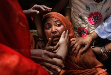 Local people console a shocked mother whose child was found under the debris of a residential building, in New Delhi, India, Wednesday, April 22, 2015. One man and a child were killed and at least nine others were injured when a three-story residential building collapsed following an explosion in a cooking gas cylinder, according to local news agency Press Trust of India. (AP Photo/Manish Swarup)
