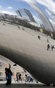 Visitors to Millennium Park take cell phone pictures beneath the Cloud Gate sculpture as the skyline is reflected in its finish, April 13, 2015, in Chicago. (AP Photo/M. Spencer Green)